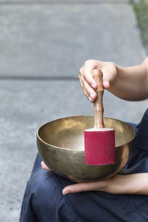 Big Tibetan singing bowl in the hands of a woman. Close up with copyspace. Medetation yoga concept. Vertical shot.