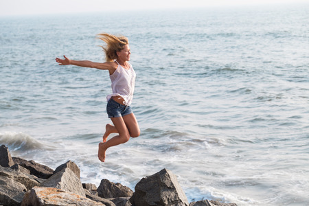 Beautiful happy mature tourist woman playful jumping on rock beach  smiling joyful outdoors. Healthy travel active lifestyle with copyspace 写真素材