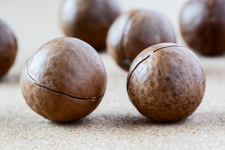 Whole Macadamia nuts on brown background, close-up. Healthy food.