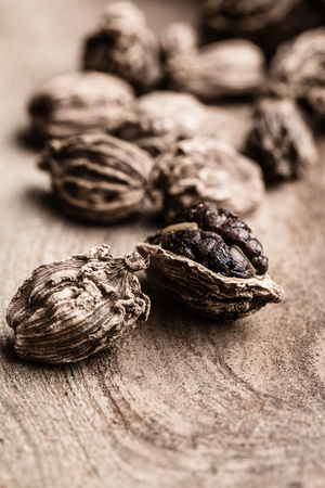Whole black cardamom on wooden background with copy space vertical. Indian spices. 写真素材
