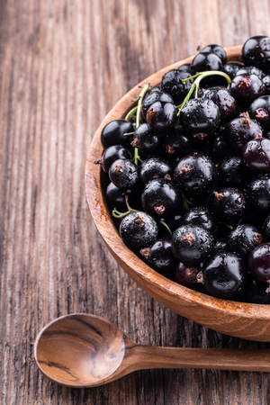 Half of big wooden bowl with fresh black currant and spoon on wooden background close-up top view . Healthy food, harvesting, vitamin, detox, vegan, vegetarian, alternative medicine.