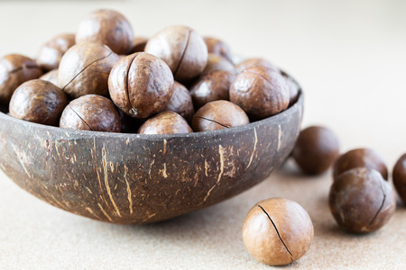 Whole Macadamia nuts in coconut bowl on corkwood background