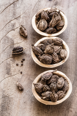 Three bowls with black cardamom on wooden background indian spice with copyspace top view