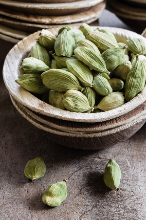 Whole green cardamom in a bowl on wooden background indian spice close-up