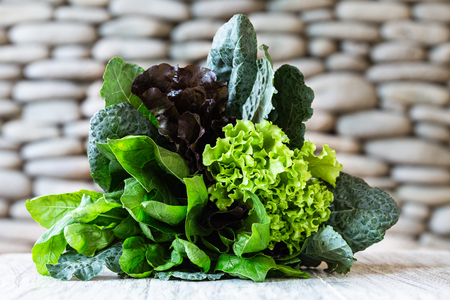 Leaves of green and red lettuce, kale, spinach, amaranth on white table with stone background. Healthy lifestyle. Green bouquet.