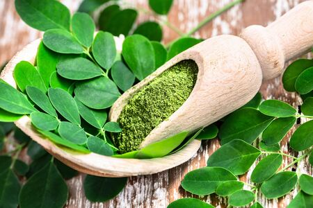 Moringa powder in wooden scoop with original fresh Moringa leaves on wooden table close-up. Stockfoto