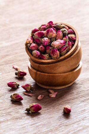 Pink red dried rose buds in wooden bowls with petals on old wooden background copy space. Healthy exotic asian organic tea.