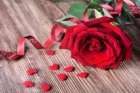 Single red rose with small hearts on wooden background with copy space love romance wedding birthday concept.