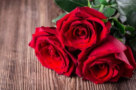 Three red roses on wooden background with copy space love romance wedding birthday concept.