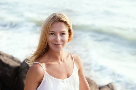 Head and shoulders portrait of happy beautiful middle aged blonde tourist woman in white top relaxing enjoying her vacation on asian beach. Imagens