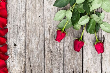 Romantic background with blooming red roses on wooden rustic table copy space. Flat lay, top view. Mothers day, Valentines day, wedding, birthday, anniversary.