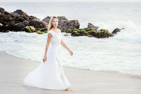 Attractive happy mature tourist blonde woman in long white dress on asian sand tropical beach smiling joyful near water. Romantic travel vacation, active lifestyle, independent and confident person with copy space.