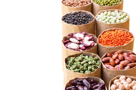 Various assortment set of indian legumes in paper sack bags isolated on white background with copy space. Vegetable protein, vegan food, healthy eating concept, design. Foto de archivo