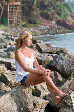 Beautiful brooding mature tourist woman sitting on rock beach  looking at sunset. Happy relax vacation. Banco de Imagens