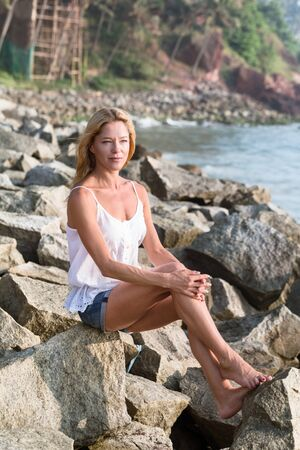 Beautiful brooding mature tourist woman sitting on rock beach  looking at sunset. Healthy travel active lifestyle.