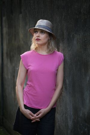 Portrait of attractive brooding blonde young woman in pink shirt and a hat standing against the old wall sunset light. Bali island travel.