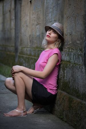 Portrait of attractive brooding sad blonde young woman in pink shirt and a hat sitting against the old wall on bali island sunset light