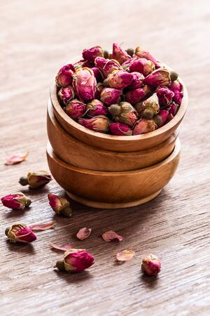 Pink red dried rose buds in wooden bowls with petals on old wooden background copyspace. Healthy exotic asian organic tea.
