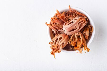 Dried whole mace in a bowl on white concrete background close-up with copy space top view. Indian spice.