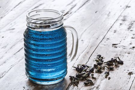 Glass jar of cold  Butterfly pea tea (pea flowers, blue pea) on old rustic table. Healthy detox herbal caffeine free fresh trendy drink. Imagens