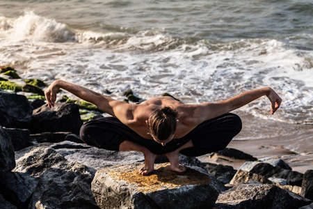 Young man in black pants doing yoga on rock beach in India morning time. Healthy life, relax, traveling, enjoy your time, way to yourself. Reklamní fotografie