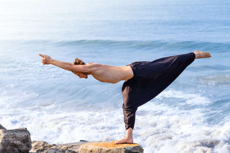 Young man in black pants doing yoga on rock beach in India standing asana virabhadrasana morning time. Healthy life, relax, traveling, enjoy your time.