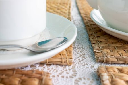 A detail of white cup of tea on a table covered with woven straw napkin in restaurant.