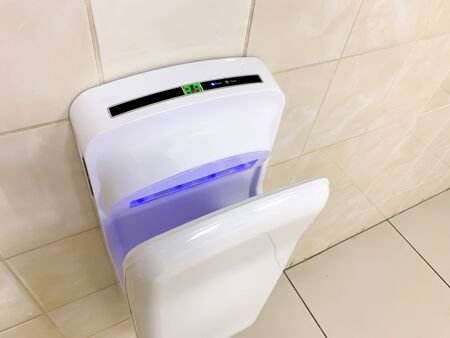 White modern hand dryer with blue lighting hanging on the wall in a public toilet, WC.