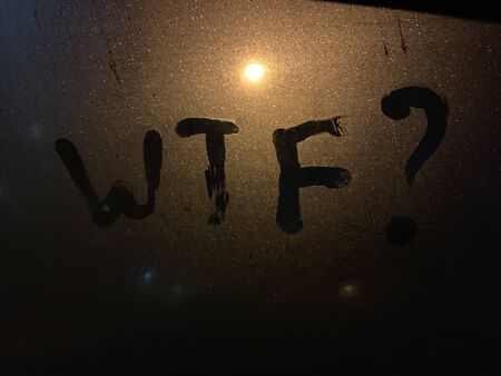 WTF handwritten sign on a frozen car window at night.