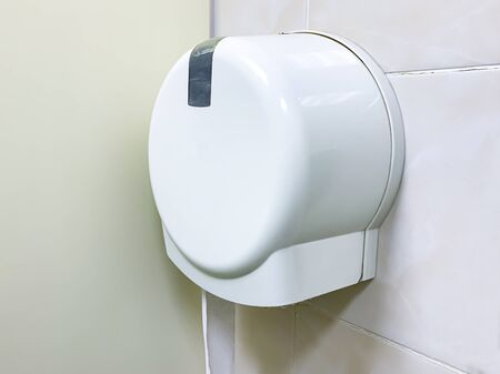 White plastic toilet dispenser on the wall of a public restroom, WC.