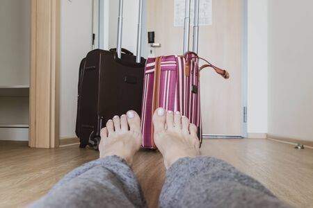 A couple of different suitcases, luggage in a hotel room standing near the door and woman legs sitting on the floor in front, travelling concept.