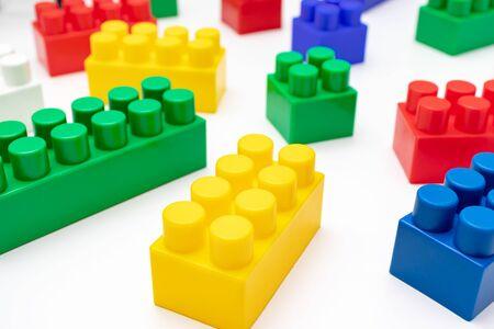 Beaucoup de briques en plastique de jouets colorés, kit de blocs pour la construction et la construction sur fond blanc, jeu pour enfants et concept de jeu. Banque d'images