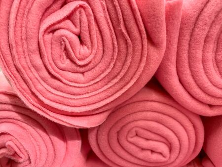 Many rolled up pink colorful fleece blankets close up in a store, home comfort concept.