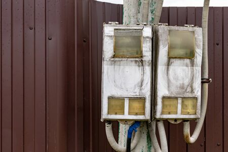 Dirty electrical shield with wires on a street pole with copy space.