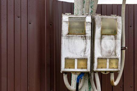 Schmutziger elektrischer Schild mit Drähten an einem Straßenpfosten mit Kopierraum.