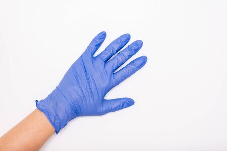 Human hand wearing blue surgical latex nitrile glove for doctor and nurse protection during patient examination on white background, copy space. Stok Fotoğraf