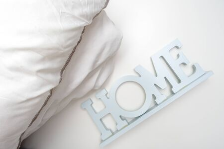 Home order background, interior details, a stack of cozy soft white bedding, pillows and blanket with a sign home, bedroom textile concept.
