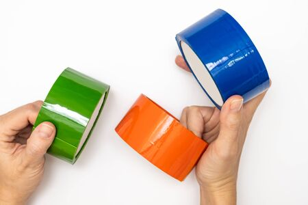 Hands holding rolls of adhesive sticky tapes of different colors, green orange and blue, materials for packaging and decoration. Stock Photo