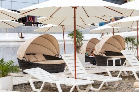 Many sun beds and umbrellas on a seashore at luxury resort, sunbathing and relaxing concept.
