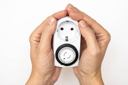 24 Hour 7 days a week mains plug timer switch european socket for energy and money saving in hands on white background.