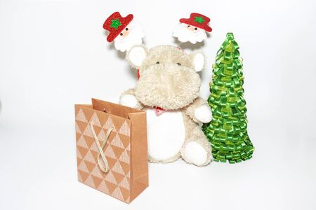 Teddy hippo, soaft stuffed toy with santa christmas decoration on a head sitting with a paper shopping bag and xmas tree on white background.