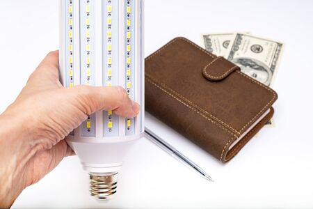 Led lamp in a hand of a person, who is searching for modern solutions of saving budget by reducing and lowering energy consumption .