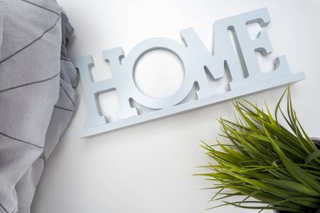 Home order background, interior details, a stack of cozy soft bedding in shades of gray, pillows and blanket with a sign home and green potted plant, home textile concept.