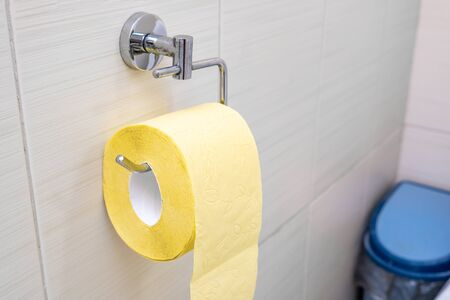 A roll of yellow toilet paper hanging on a wall fixture in a rest room, digestive problems concept.