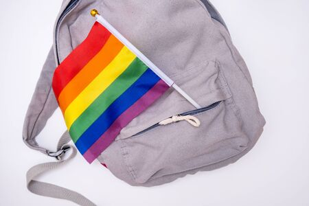 An LGBT gay pride rainbow flag in a pocket of a backpack, travelling concept.