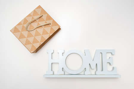 A sign home and a paper craft shopping bag on white background, buying home concept. Stock fotó