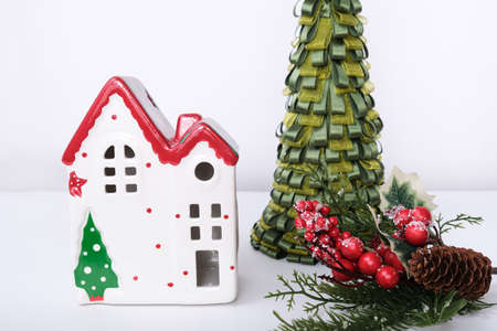 Christmas background with red ceramic decorative house, pine fir tree and new year decorations against white. Banque d'images