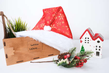 Christmas background with red ceramic decorative house, santa hat and wooden decorations against white.