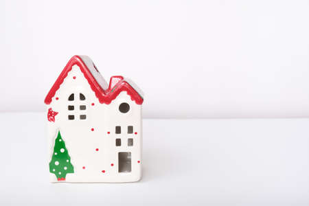 Christmas background with red ceramic decorative house against white with copy space.