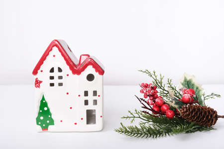 Christmas background with red ceramic decorative house and new year decorations against white.